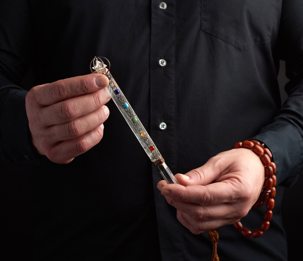 Person holding a crystal chakra wand
