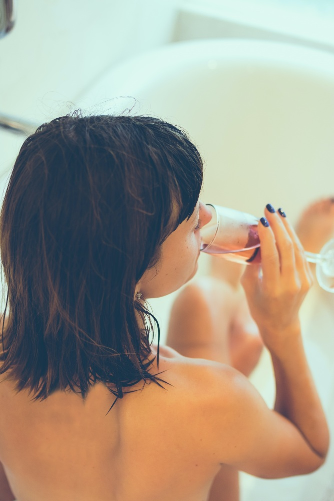Woman having a bath drinking a glass of champagne