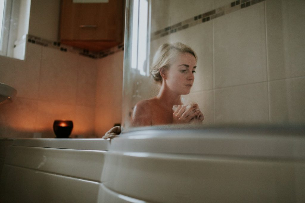Woman having a bath with a candle lit